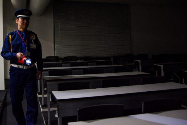 夜に教室の巡回をする警備員