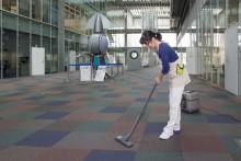 学内で掃除機をかける清掃担当のスタッフ