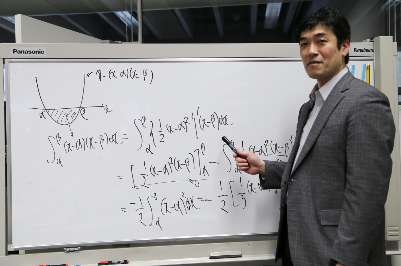 ホワイトボードに数式を書く高村先生