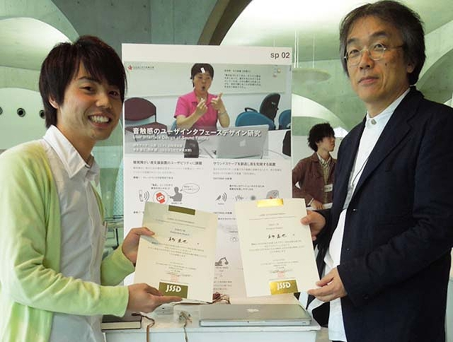 賞状を手にする本多さんと岡本誠教授