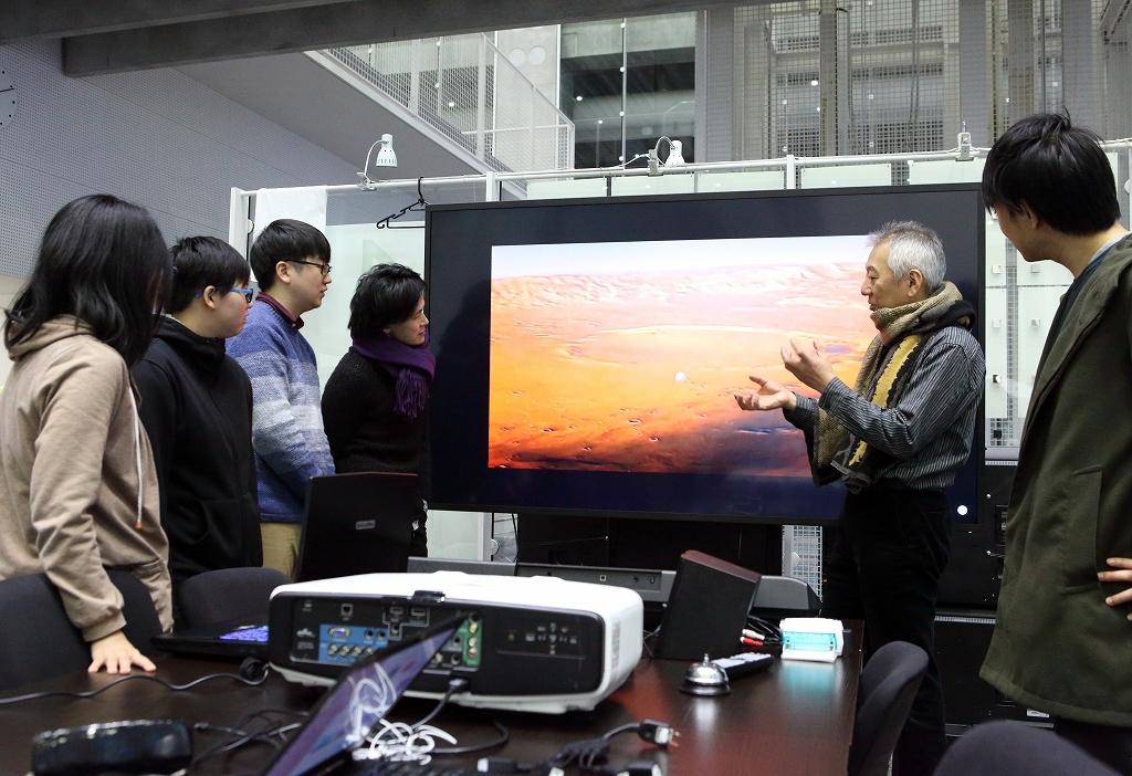 大きなスクリーンの前で学生と議論する平田教授