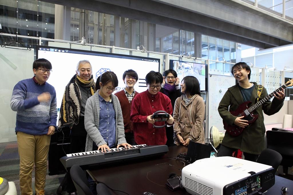 鍵盤を弾く学生、ギターを弾く学生とその他学生、教授。集まって楽しそうな様子