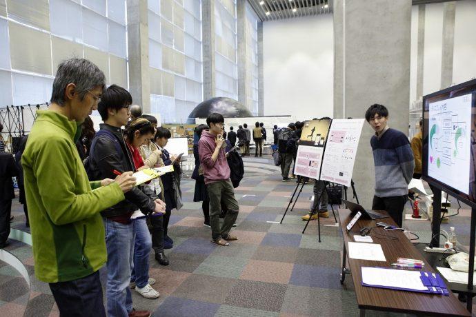 集まる学生、先生の前でプロジェクト学習の成果を発表する学生