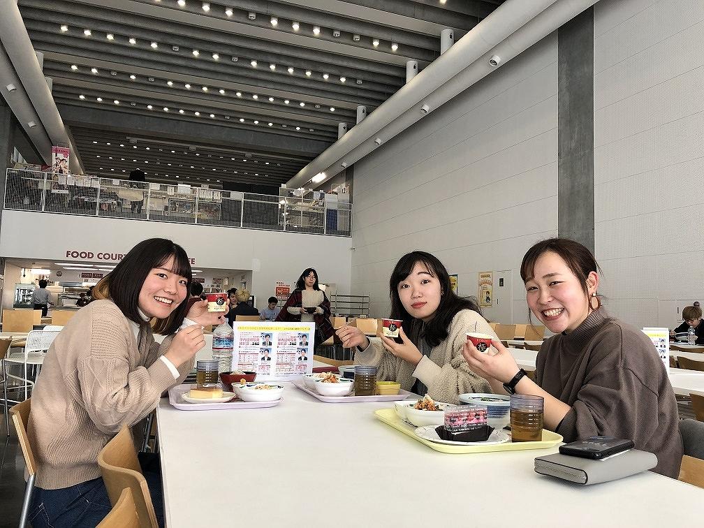 ひじき煮を持って笑顔の女子学生たち