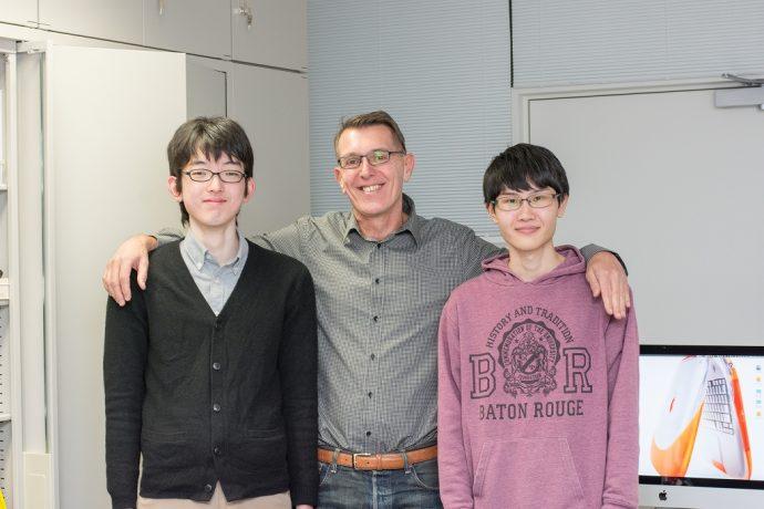 両脇の学生と肩を組んで笑顔のヴァランス教授